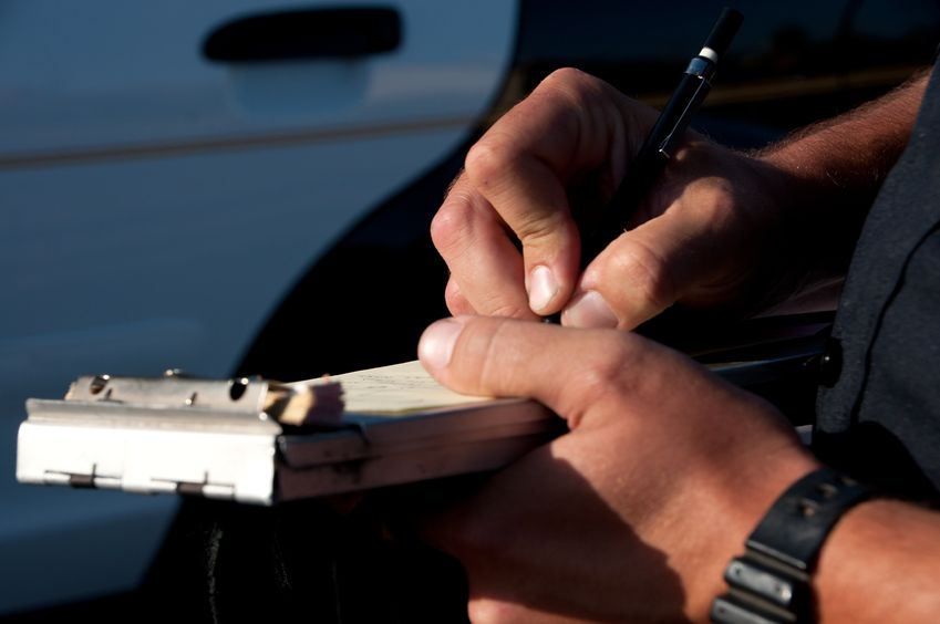 a close up of a police officer writing a traffic ticket.